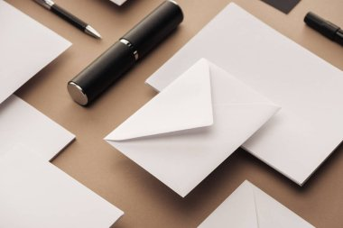 Empty sheets of paper, case, pen and envelopes on beige background
