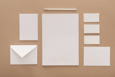 Envelope, pencil, cards and sheets of paper on beige background
