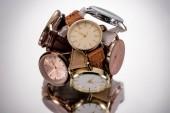 Selektivní fokus náramkové švýcarské hodinky na šedém pozadí