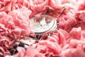 Švýcarské Náramkové hodinky ležet na kvete růžovými květy