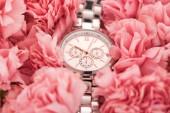 elegantní náramkové hodinky ležet na kvetoucí růžové karafiáty