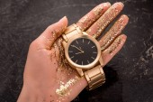 Photo cropped view of golden wristwatch in hand of woman