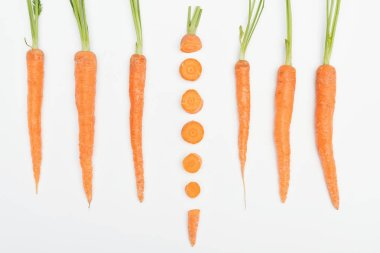 top view of composition with whole carrots with one sliced carrot in center isolated on white