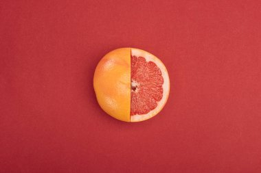 top view of fresh ripe partially cut grapefruit on red background