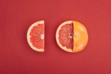 Top view of grapefruit slice and partially cut grapefruit on red background stock vector