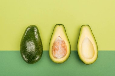 top view of whole avocado and avocado halves on bicolor background