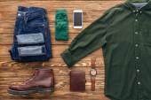 Piatto posare con jeans, camicia verde e smartphone su fondo di legno