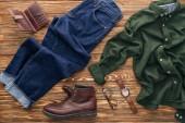 Vista superiore della camicia verde, jeans e portafoglio in pelle su fondo di legno