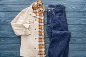 Photo Top view of checkered shirt, jacket and jeans on wooden background