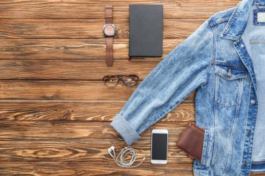 Flat lay with denim jacket, smartphone and accessories on wooden background stock vector