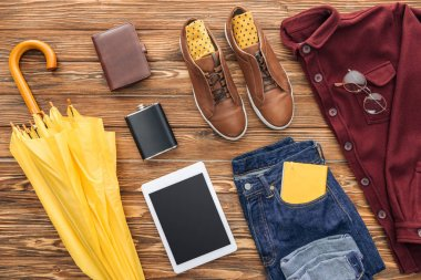 Flat lay with male clothes, digital tablet and yellow umbrella on wooden background stock vector