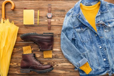 Flat lay with denim jacket, yellow umbrella and textbook on wooden background