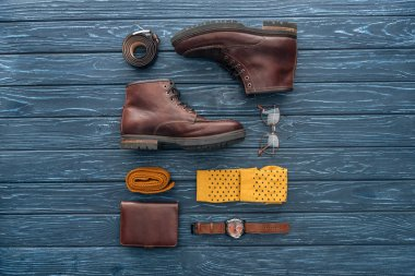 Flat lay with brown boots, wallet and glasses on wooden background stock vector