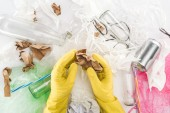 Photo Cropped view of man holding paper among can, glass bottles, plastic bags, paper strips and plastic tubes