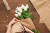partial view of on florist cutting craft paper while making spring bouquet on wooden background