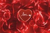 Fotografia vista ravvicinata del bello cuore rosso con scritta love e nastri decorativi, giorno di San Valentino sfondo