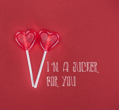 Two heart shaped lollipops on red background with