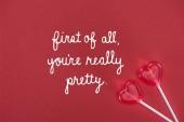 pohled shora ze dvou lízátka ve tvaru srdce na červeném pozadí s nápisem za prvé, jste opravdu hezká, valentines day koncept
