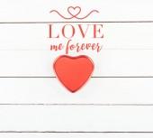 Draufsicht auf rote Herzschachtel mit Love me forever -Schriftzug auf weißem Holzhintergrund, Valentinstag-Konzept