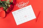 vista superiore di rose e calendario con 14 febbraio data contrassegnata con cuore isolato su colore rosso con la scritta Buon San Valentino