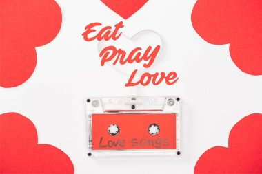 Top view of audio cassette with 'love songs' lettering and heart shaped cards isolated on white, st valentines day concept with