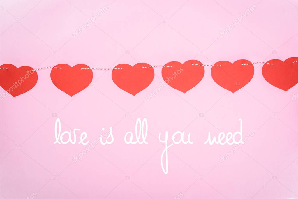 Beautiful decorative red hearts hanging on rope on pink background with