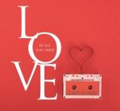 erhöhte Ansicht der Audiokassette mit Schriftzug Liebeslieder und Herzsymbol aus Klebeband isoliert auf rotem, Valentinstag-Konzept mit Liebe ist alles, was du brauchst Schriftzug