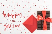 view from above of envelope and delicious chocolate wrapped by festive ribbon isolated on white, st valentine day concept with love lettering
