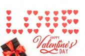 Fotografia lay flat con lettering fatta di simboli del cuore di amore e cioccolato avvolta da nastro festivo isolato su bianco, felice San Valentino con scritta love