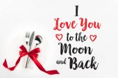 Photo elevated view of fork, knife and spoon wrapped by red festive bow on plate isolated on white, st valentine day concept with I love you to the moon and back lettering