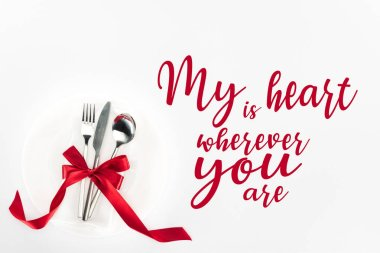 Elevated view of fork, knife and spoon wrapped by red festive bow on plate isolated on white, st valentine day concept with