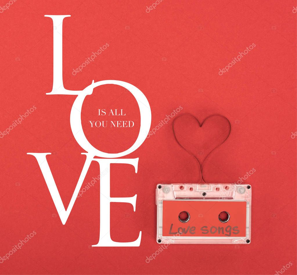 Elevated view of audio cassette with lettering love songs and heart symbol made of tape isolated on red, st valentine day concept with