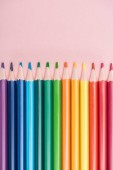 Fotografie rainbow multicolored pencils arranged in horizontal line on pink background, lgbt concept