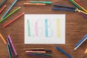 fehér papír, kézzel írott szó LMBT, színes ceruza, és barna fa felületén filctollak