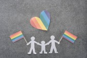 Photo paper cut same sex family with rainbow colored flags and paper heart on grey background, lgbt concept