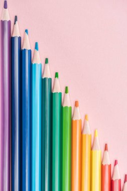 Top view of rainbow multicolored pencils arranged in diagonal line on pink background, lgbt concept stock vector