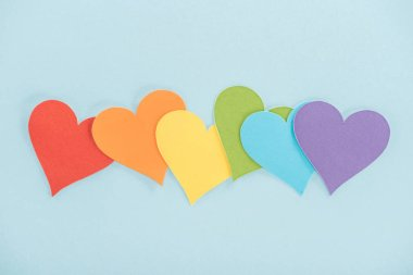 rainbow colored paper hearts on blue background, lgbt concept