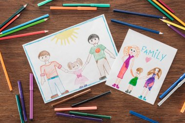 Color pencils and felt pens, and white papers with drawings of same sex families and