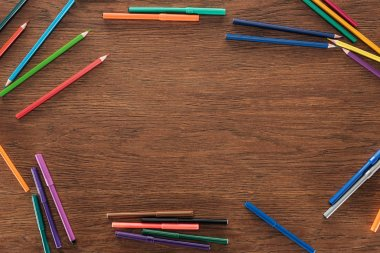 color pencils and felt pens on brown wooden surface