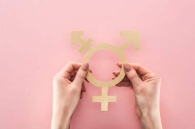 partial view of woman holding gender sign on pink background, lgbt concept