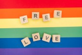Fotografie top view of free love lettering made of  wooden cubes on paper rainbow background