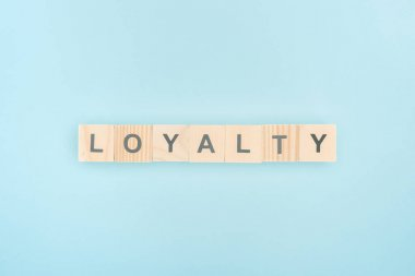 top view of loyalty lettering made of wooden cubes on blue background