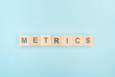 top view of metrics lettering made of wooden cubes on blue background