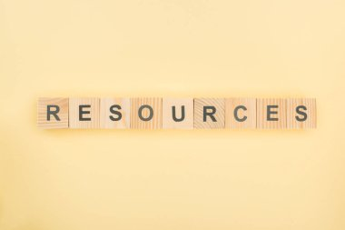 top view of resources lettering made of wooden cubes on yellow background