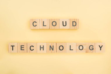 top view of cloud technology lettering made of wooden cubes on yellow background