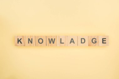 top view of knowledge lettering with mistake made of wooden cubes on yellow background
