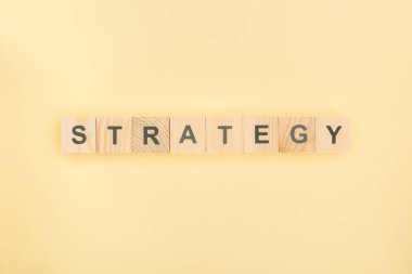 Top view of strategy lettering made of wooden cubes on yellow background stock vector