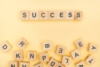 Top view of success lettering with wooden cubes on yellow background stock vector