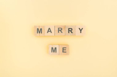 top view of marry me lettering made of wooden blocks on yellow background