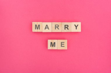 Top view of marry me lettering made of wooden cubes on pink background stock vector